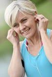 Современная старшая женщина слушая к музыке готовой для jogging Стоковая Фотография