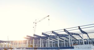 Современная строительная площадка storehouse, структурная стальная структура нового коммерчески здания против ясной сини сток-видео