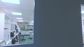 Современная фармацевтическая лаборатория Pov ученого смотря в комнате лаборатории