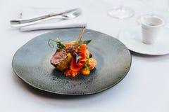 Современная французская кухня: Зажаренные в духовке шея & шкаф овечки служили с морковью, желтым карри, который служат в черной к стоковые фотографии rf