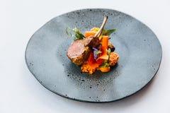 Современная французская кухня: Зажаренные в духовке шея & шкаф овечки служили с морковью, желтым карри, который служат в черной к стоковое фото rf