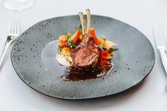 Современная французская кухня: Зажаренные в духовке шея & шкаф овечки служили с морковью, желтым карри и соусом овечки послуженны стоковое фото