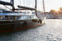 Современная чернота красный парусник в гавани Канн на заходе солнца Стоковые Изображения