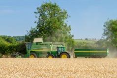 Современное вырезывание жатки зернокомбайна John Deere подрезывает с трактором и трейлером Стоковая Фотография RF