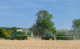 Современное вырезывание жатки зернокомбайна John Deere подрезывает с трактором и трейлером Стоковое фото RF