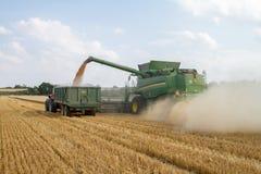 Современное вырезывание жатки зернокомбайна John Deere cts 9780i подрезывает ячмень пшеницы мозоли работая золотое поле Стоковое Изображение
