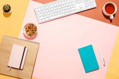 Современное женственное домашнее место для работы Плоский состав положения клавиатуры, кактуса, дневника с ручкой и чашки чаю на  стоковые фото