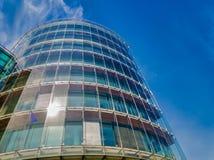 Современное круглое здание с отраженными небом и облаком в стеклянном окне с пирофакелом объектива стоковое фото rf