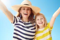 Современное ликование матери и ребенка против голубого неба стоковые фотографии rf