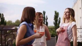3 современное, молодые женщины говорящ и выпивающ оранжевые коктеили от бокалов Делить рассказы и смеяться над акции видеоматериалы