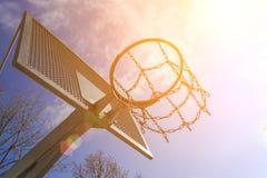 Современное особопрочное кольцо баскетбола металла на предпосылке голубого неба и солнца Стоковые Фотографии RF