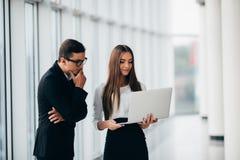 Современные бизнесмены работая на компьтер-книжке в зале офиса с панорамными окнами обсуждают будущие изменения на компьтер-книжк Стоковые Фото