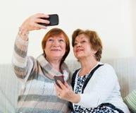 Современные зрелые женщины используя мобильный телефон Стоковые Изображения RF