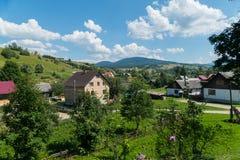 Современные и старые частные жилые дома с графиками сада и сады фруктового дерев дерева в деревне на долине горы Стоковые Изображения RF