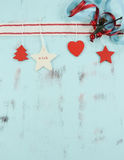 Современные красные и белые украшения рождества смертной казни через повешение на предпосылке aqua голубой деревянной вертикально Стоковое фото RF