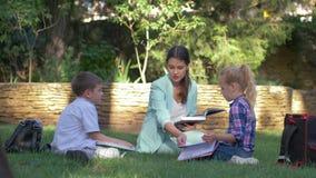 Современные методы образования, зрачки мальчик одноклассника и девушка с учебником и болтовней гувернера женским прочитанным во в сток-видео