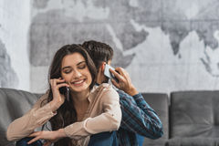 Современные пары используя smartphones дома Стоковое Фото