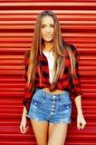 Современные представления молодой женщины перед красной предпосылкой стены Сексуальный w Стоковые Фотографии RF