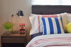 Современные спальня с красочными striped подушками и деревянный Стоковое Изображение RF