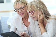 Современные старшие женщины используя таблетку Стоковая Фотография