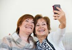 Современные счастливые зрелые женщины используя мобильный телефон Стоковое Изображение
