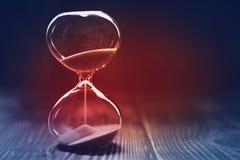 Современные часы с темной предпосылкой, песком trickling через шарики кристаллического стекла песка, с красным светом в центре стоковое фото rf