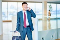 Современный азиатский бизнесмен говоря телефоном стоковое фото