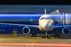 Современный белый самолет пассажира стоя на месте для парковки на ноче и получает готовым для всходя на борт пассажиров внутри Стоковые Фотографии RF