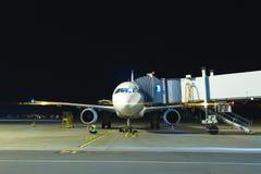 Современный белый самолет пассажира стоя на месте для парковки на ноче и получает готовым для всходя на борт пассажиров внутри Стоковая Фотография RF