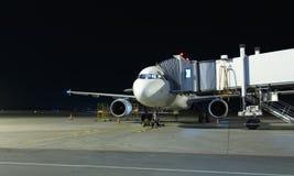 Современный белый самолет пассажира стоя на месте для парковки на ноче и получает готовым для всходя на борт пассажиров внутри Стоковое Фото