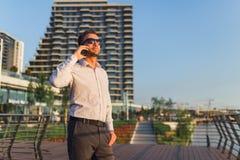 Современный бизнесмен вызывая на смартфоне перед офисными зданиями стоковые изображения