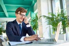 Современный бизнесмен говоря телефоном пока работающ стоковое фото