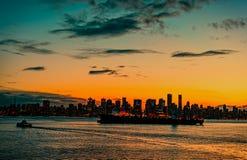 Современный город ночи против предпосылки оранжевого красного цвета пасмурного Стоковые Фото