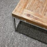 Современный деревянный стол на ковре связанном серым цветом стоковое изображение rf