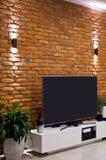 Современный дизайн домашней комнаты с красной кирпичной стеной и плоским телевидением приведенным стоковое изображение