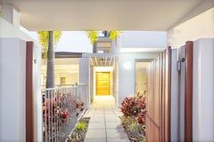 Современный домашний вход с деревьями цветка и полом плитки стоковая фотография rf