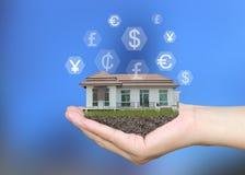 Современный дом в руках бизнесмена на голубых предпосылке и ha Стоковое Изображение RF