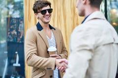 Современный друг приветствию молодого человека в улице, усмехаясь стоковое изображение