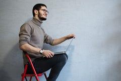 Современный думая бородатый хипстер используя ноутбук, сидя на красных металлических лестницах стоковые изображения rf