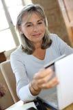 Современный зрелый ходить по магазинам женщины онлайн от дома Стоковое Изображение