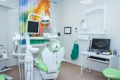 Современный зубоврачебный офис с зеленым стулом и профессиональными инструментами Стоковая Фотография