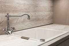 Современный дизайнерский водопроводный кран хрома над белой кухонной раковиной Стоковые Фото