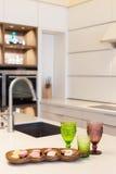 Современный дизайнерский водопроводный кран хрома на фоне новых шкафов сделанных из древесины с встроенной печью Стоковые Фото