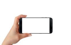 Современный изолированный черный умный телефон в руке женщины в горизонтальном положении стоковая фотография