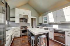 Современный интерьер кухни стиля с коричневыми и белыми шкафами стоковая фотография