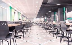 Современный интерьер столовой или буфета с стульями и таблицами Стоковое Изображение RF