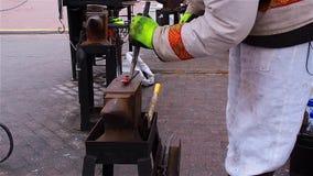 Современный кузнец в столице демонстрирует их способность изготовить крепежные детали на ярмарке рождества видеоматериал