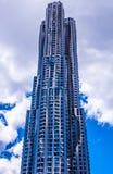 Современный металлический сияющий небоскреб с волнистым фасадом формы и пасмурным голубым небом стоковые изображения