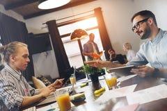 Современный молодой бизнесмен 2 сидит вокруг таблицы и работает на компьтер-книжке Стоковая Фотография RF