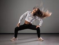 Современный молодой красивый танцор представляя на предпосылке студии Стоковые Фото